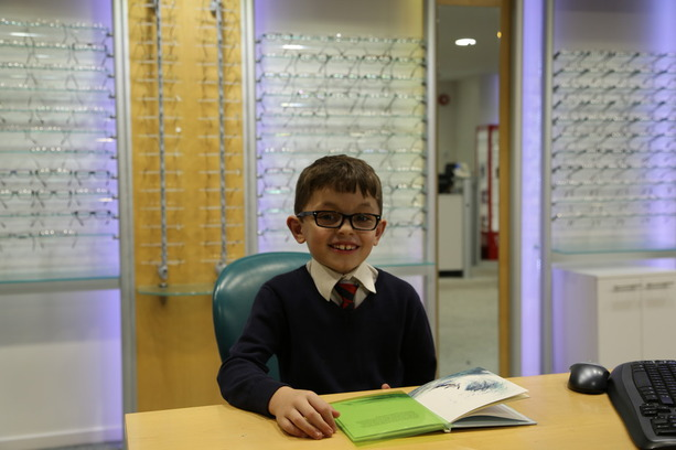 Isaac Randall reading with his coloured overlay following Irlen screening examination/test at Buchanan Optometrists, Kent